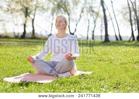 Absolute Tranquility. Nice Aged Woman Meditating While Sitting In The Grass
