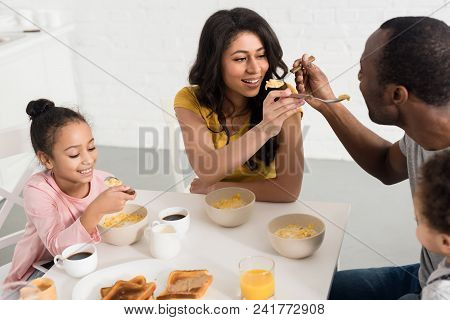 Wife And Husband Feeding Each Other While Having Breakfast With Kids