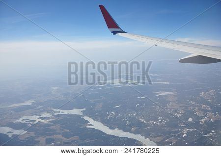Norwegian Landscape Under The Wings Of An Airplane Flying Over The Clouds.
