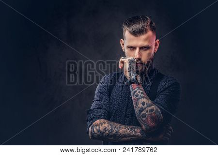 Pensive Handsome Old-fashioned Hipster In A Blue Shirt And Suspenders, Standing With Hand On Chin In