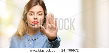 Consultant of call center woman in headphones annoyed with bad attitude making stop sign with hand, saying no, expressing security, defense or restriction, maybe pushing
