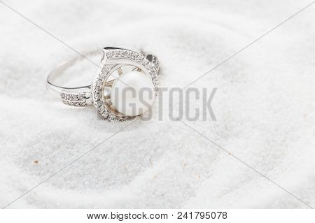 Silver Ring With Big Pearl And Diamonds On White Sand. Copy Space