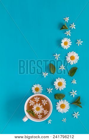 Cup Of Tea With Fresh Flowers Blossom Bouquets On Blue Surface. Flat Lay, Top View Food Floral Backg