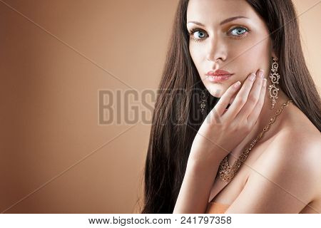 Portrait of woman with gold jewelry on beige background