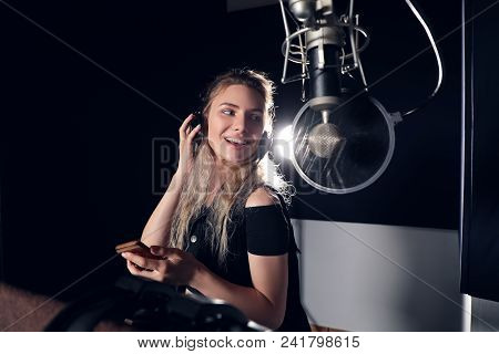 Create Your Music! Beautiful Young Girl Smiling, While Reading Lyrics And Singing A Song With A Mobi