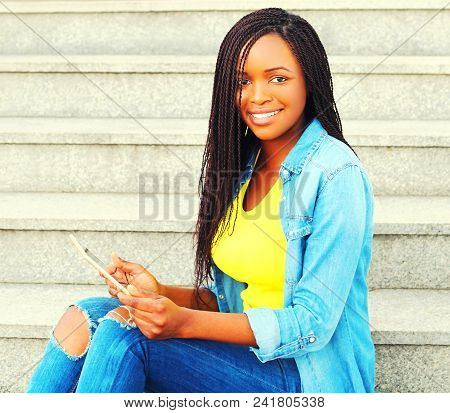 Fashion Smiling African Woman Using Tablet Pc Computer In The City