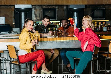 Group Of Multiethnic Friends With With Various Alcohol Beverages Spending Time Together In Bar