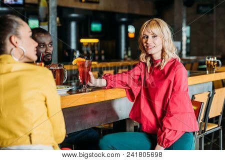 Young Multiethnic Friends Spending Time In Bar And Drinking Alcoholic Beverages