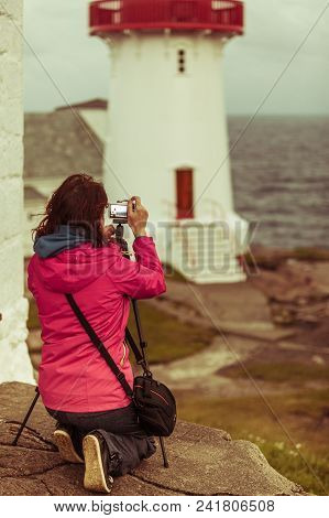 Female Tourist Traveler Taking Photo At Historic Red White Lighthouse On The Edge Of Rocky Sea Coast