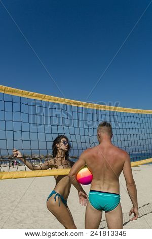 Young Sporty Active Couple Stand Near Volleyball Net Play Game On Summer Day. Couple Have Fun Playin