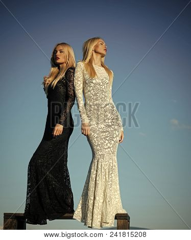 Sensual Woman. Two Girls With Long Blond Hair Posing On Blue Sky. Fashion And Beauty. Choice, Decisi