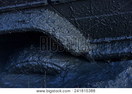 Fragment of car stuck in dirt, close up. Wheel in deep puddle of mud overcomes obstacles. 4x4 racing concept. Offroad tire covered with mud on nature background. poster