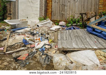 Large Pile Of Rubbish, Rotting After Being Fly Tipped And Left In An Urban Alleyway. Demonstrates An