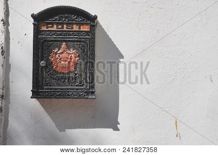 Black Vintage Metal Mailbox With Red Bas-relief In The Middle On A White Wall, A Slanting Shadow Fal