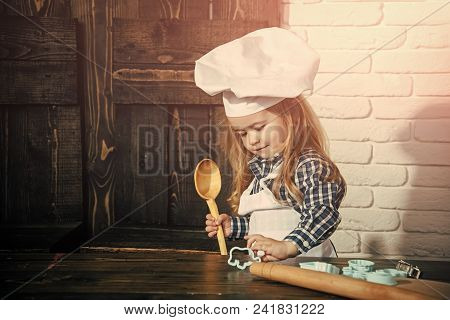 Happy Kid Having Fun. Boy Cook In Chef Hat And Apron In Kitchen. Child Using Spoon, Rolling Pin And