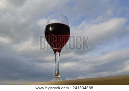 Red Wine In A Glass On The Outdoor Deck Railing With A Cloudy Sky Background