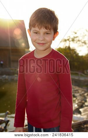 Outdoor portrait of smiling little boy in red.