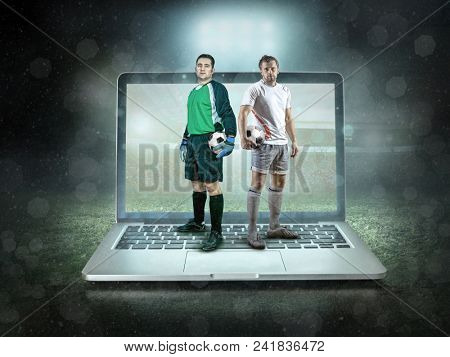 Caucassian soccer Players stay with ball in a professional sport game play on the laptop in football under stadium lights.