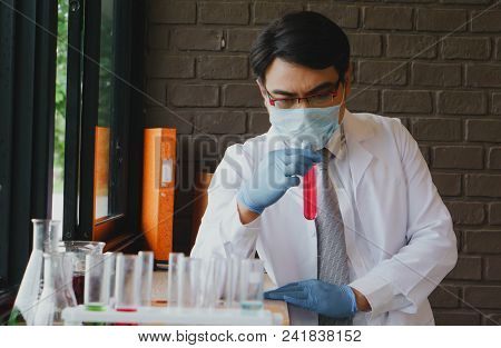 Medicals Or Scientific Laboratory Researcher Performs Tests With Red Liquid In Lab. Laboratory Equip