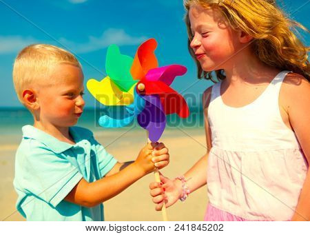 Brother and sister playing with a pinwheel