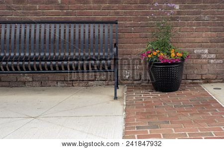 Community City Park Bench On Sidewalk Or Pathway Beside Decorative Planter Ready For Someone To Sit