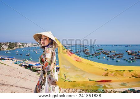 Vietnam Woman Wearing Ao Dai Culture Traditional And Conical Hat Wait At The Harbor At Mui Ne In Vie
