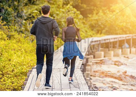 Young Asian Couple Running On Wooden Bridge In The Morning,helping And Relaxing Concept.