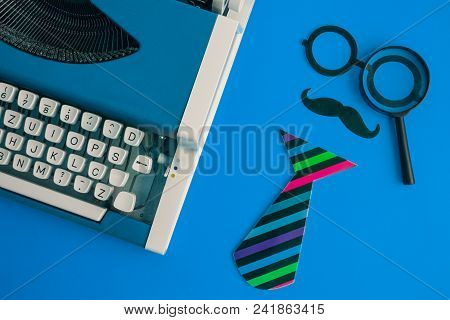 Flat Lay Of Vintage Blue Typewriter And Paper Props In Form Of Retro Hipster Man With Magnifying Gla