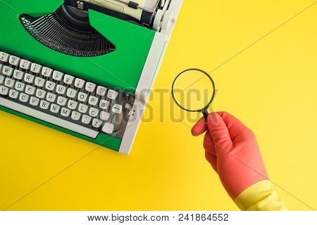 Hand Wearing Rubber Gloves And Holding Magnifier With Typewriter In The Background Minimal Creative