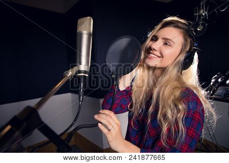 Music Is All Around! Young Cheerful Pretty Smiling Blonde Woman Recording A Song In A Professional S