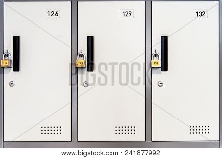 Locked white lockers with padlocks