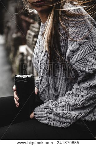 Young Beautiful Girl In A Warm Knitted Sweater And Boots Posing On The Street, On The Street Porttra
