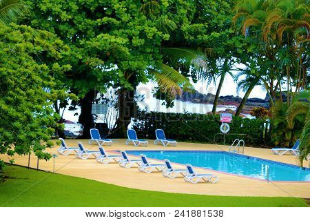 May 16, 2018 In Hilo, Hi:  Lawn Chairs Surrounding A Pool Besides Manicured Gardens Overlooking The