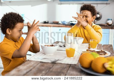 Having Fun. Upbeat Little Boys Sitting At The Table, Thumbing Their Noses At Each Other And Laughing