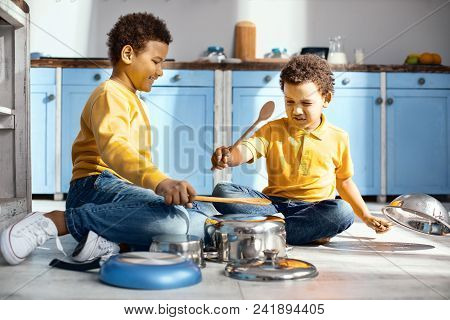Wannabe Musicians. Upbeat Young Boys Sitting On The Kitchen Floor And Pretending To Be Musicians Whi