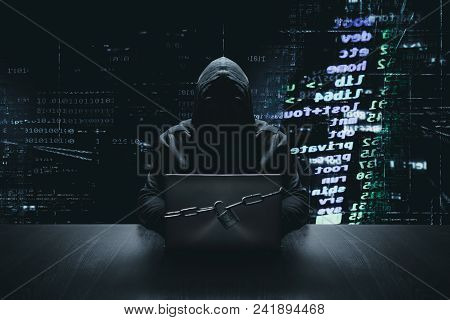 Anonymous Hacker With Locked Computer In Front Of Binary Code Background