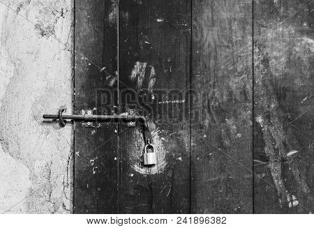 Close Up View Of Iron Lock On An Weathered Wooden Door.