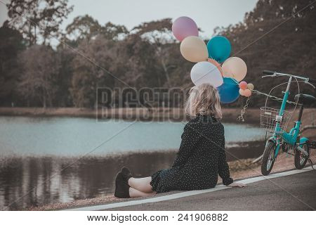 Teenager Girl Sitting Alone In The Park With Balloon On Moutain Background.