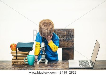 Kid Boy Looks In Microscope. Wunderkind Concept - Smart Small Boy, Scientist Child Working With Micr