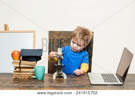 Wunderkind Concept. Smart Small Boy, Scientist Child Works With Microscope, Laptop. Concentrated Kid