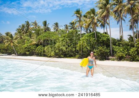 Young Woman In Bikini Surfing On Tropical Beach In Asia. Girl On Surf Board On Ocean Wave. Active Wa