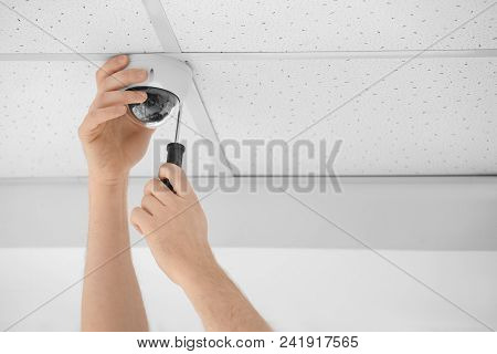 Technician Installing Cctv Camera On Ceiling Indoors, Closeup
