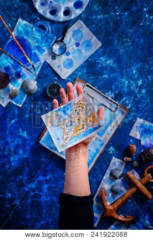 Artist Holding A Hand-painted Fantasy Island Map. Marine Watercolor Concept. Creative Artist Workpla