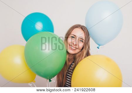 Blonde Girl Smiling And Looking At Camera Between Multicolored Balls On White Background. Studio Por
