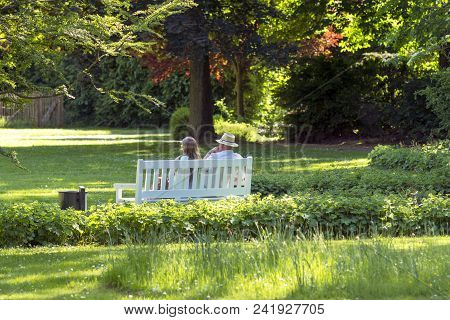 Beautiful Happy Couple Sitting In The Park On A Bench
