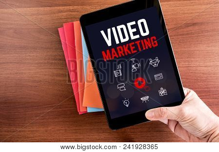 Top View Of Hand Holding Tablet With Video Marketing Word Over Color Notebook On Wooden Table Top,di