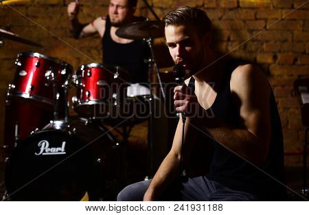 Guy Near Scene Holds Microphone And Sings. Singer Or Star Sitting On Scene And Sings. Rock Music And