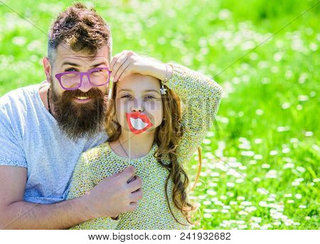 Dad And Daughter Sits On Grass At Grassplot, Green Background. Fatherhood Concept. Family Spend Leis