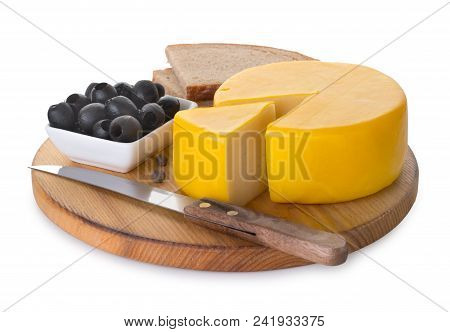 Sliced Round Head, Wheel Of Delicious Cheese On A Round Cutting Board With Knife, Bread And Olives I