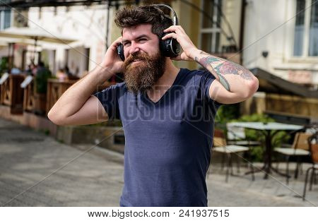 Man With Long Beard And Mustache With Wireless Headphones On Head, Defocused Urban Background. Hipst